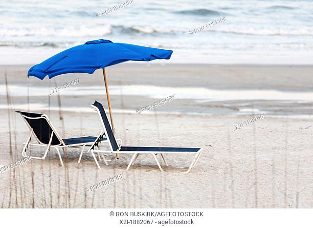 Empty beach lounge chairs under beach umbrella at Amelia Island, Florida