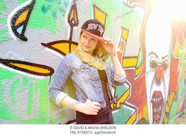 Young woman at a graffiti wall, Nuremberg, Bavaria, Germany, Europe