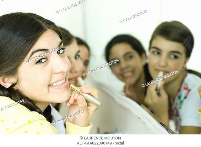 Young female friends putting on make-up