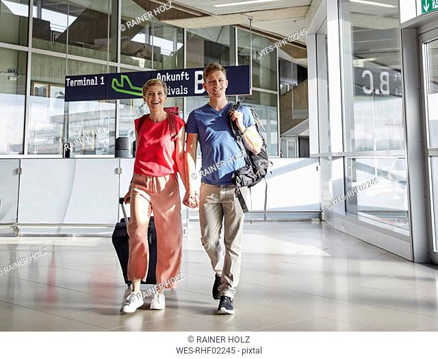 Happy couple walking hand in hand at the airport