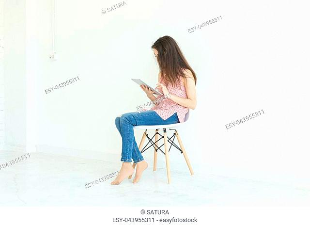 Technology, people concept - young woman sitting on chair and reading digital tablet or surfing the net