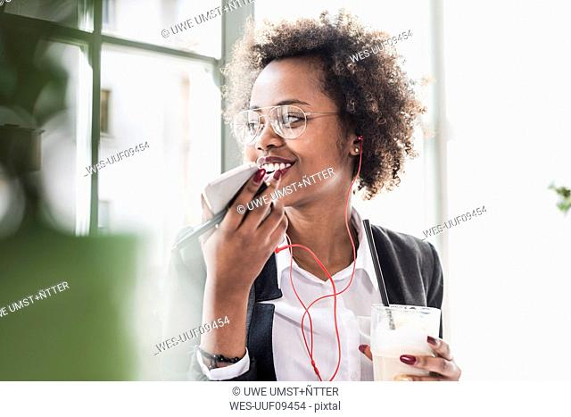Smiling young woman using cell phone in a cafe