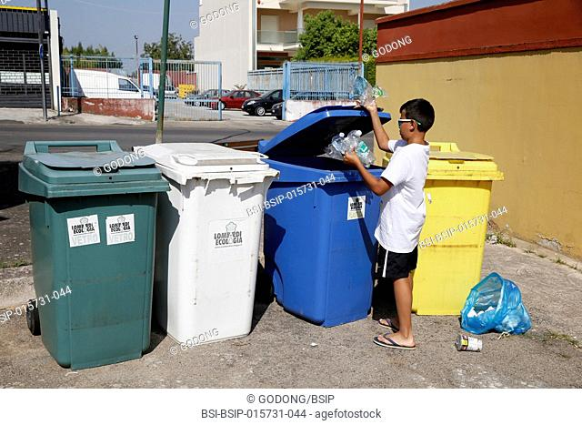 11-year-old boy throwing garbage into recycling bins in Salento, Italy