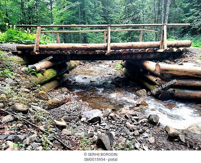 Mountain river flowing under the wood bridge nature