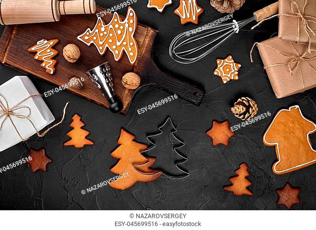 Christmas homemade gingerbread cookies, spices and cutting board on dark background with copy space for text top view. Holiday, celebration and cooking concept
