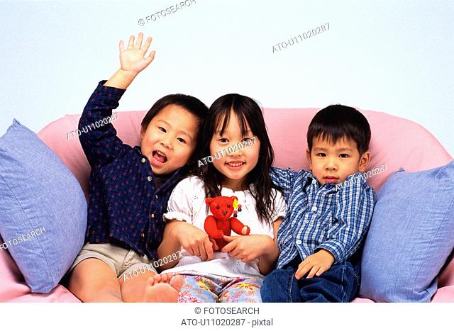 Portrait of Two Little Boys and One Girl in the Middle, Sitting on a Sofa, Smiling, Looking at Camera, Front View