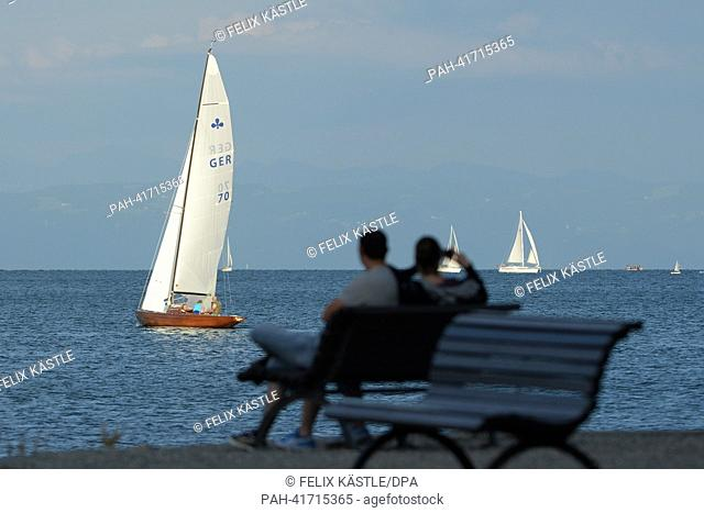 Two people sit on a bench on the harbor promenade while sail boats pass in the background shortly before sunset in Konstanz, Germany, 13 August 2013