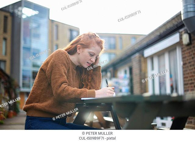 Woman sitting at picnic bench writing