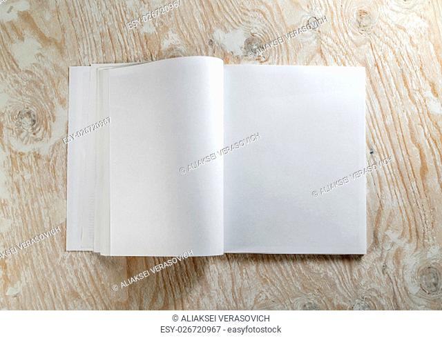 Blank opened book on light wooden background with soft shadows. Template for design presentations and portfolios. Top view