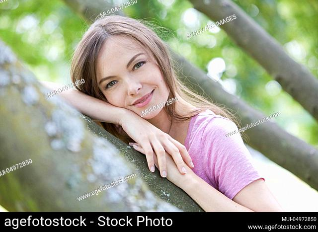 Woman is standing on a tree