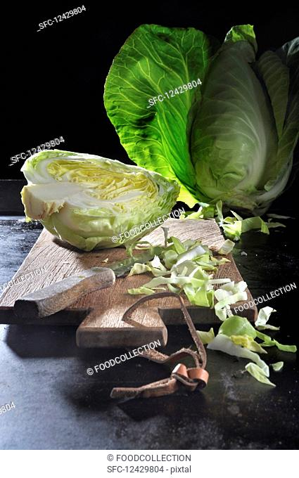 Pointed cabbage, whole, halved and sliced, on a chopping board with a knife on a black baking tray