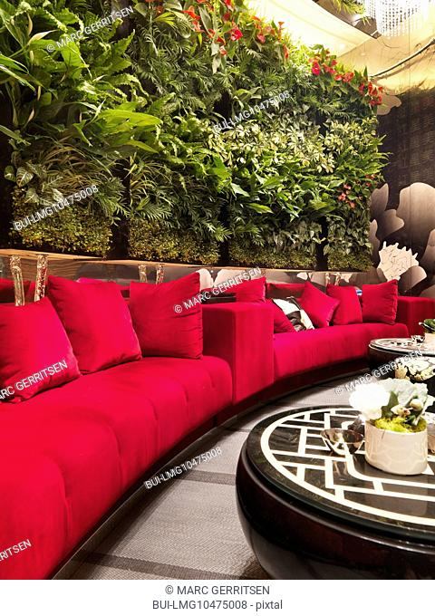 Walled red sofa with plants in restaurant