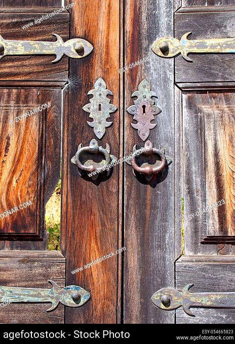 a close up of old cracked and broken wooden exterior double doors with ornate iron and brass handles keyholes and hinges