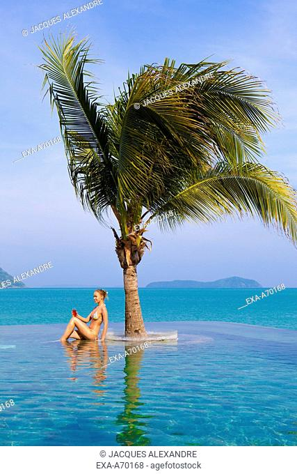 Woman sitting under palm tree in the pool having a drink