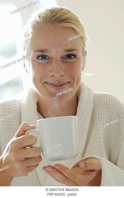Young woman with dressing and coffee mug