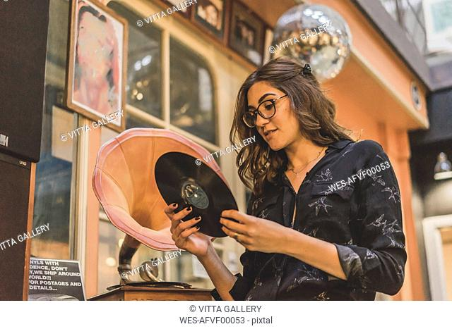 Portrait of smiling young woman standing in front of antique shop looking at gramophone record