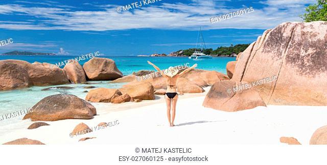 Woman arms rised, wearing black bikini and beach hat, enjoying amazing view on Anse Lazio beach on Praslin Island, Seychelles