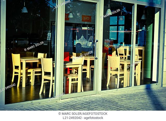 Empty restaurant . Wooden tables and chairs inside. Sunlight. Barcelona, Catalonia, Spain