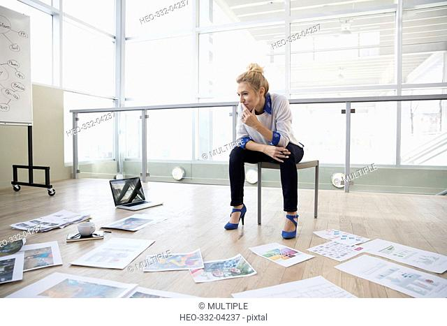 Creative female designer reviewing proofs and paperwork on office floor