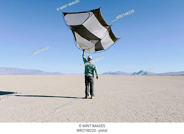 Man holding a capsule pod camping tent above his head in the open space of the desert