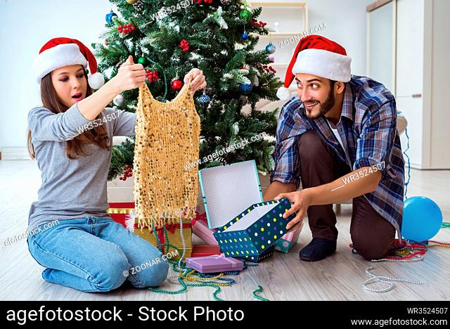 Young woman receiving dress as christmas gift