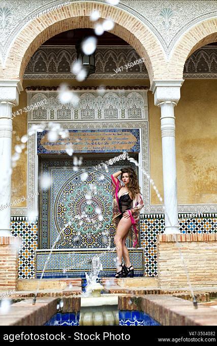 Portrait a sexy girl posing in a black bodysuit in an Arab courtyard