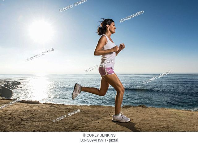 Mid adult woman jogging along cliff