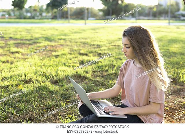 Teenage girl sitting on the lawn with a laptop. Shot with natural light