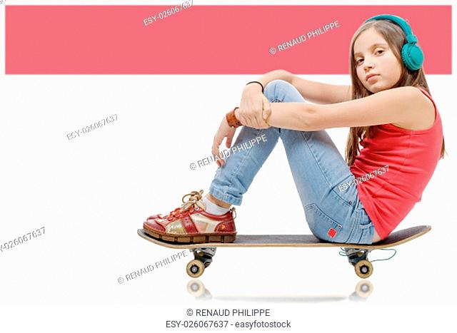 a pretty younggirl posing with a skateboard, seat on skate