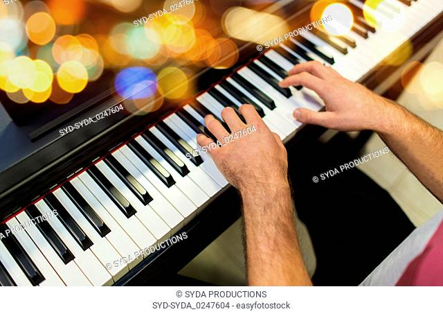 close up of male hands playing piano