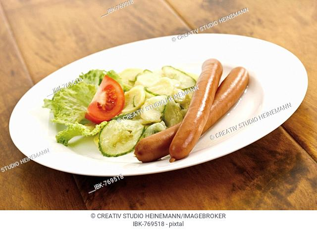 Plate of sausages with potato salad on a wooden table