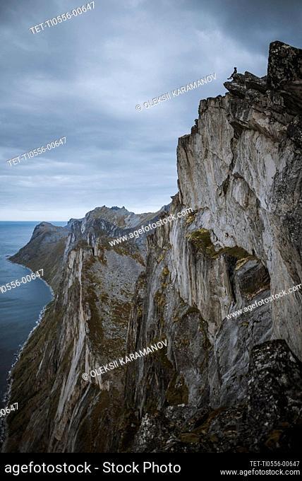 Norway, Senja, Man sitting on the edge of steep cliff on top ofSeglamountain