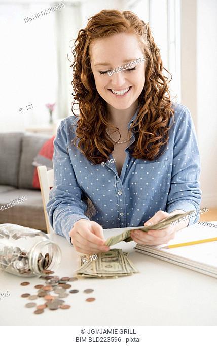 Caucasian woman counting money from savings jar