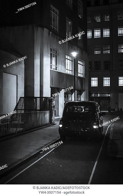 Black cab in a narrow street at night, Holborn, London, England, UK
