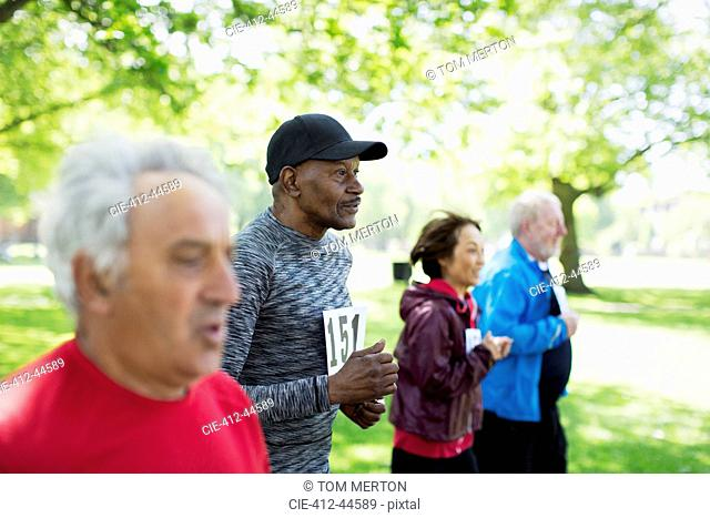 Active seniors running sports race in park
