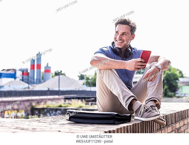Businessman sitting on a wall, using smartphone