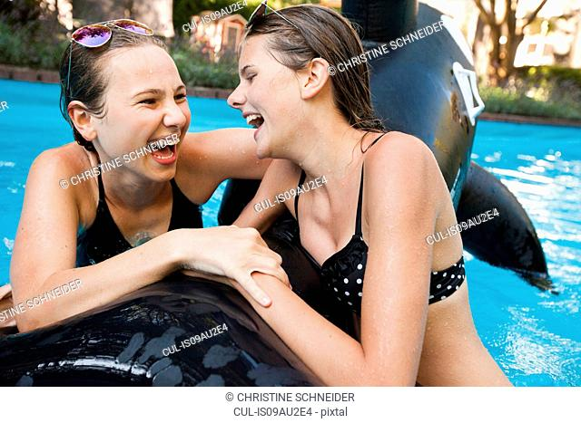 Two teenage girls holding onto inflatable fish in swimming pool