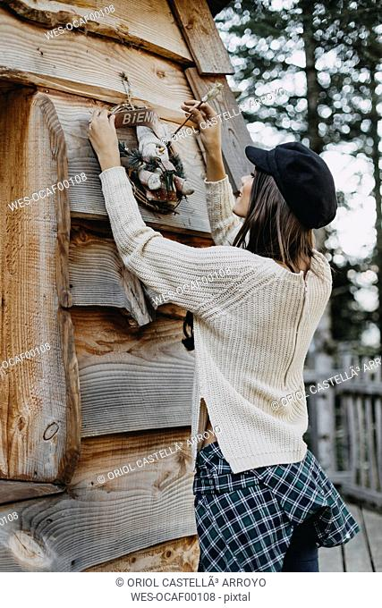 Young woman decorating wooden house with Christmas decoration