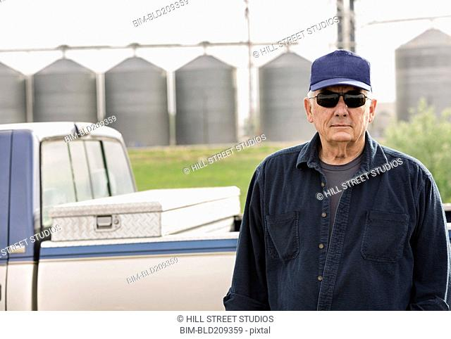 Caucasian farmer standing by truck