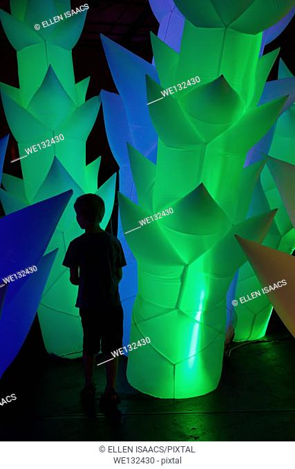 Boy exploring forest of inflated neon trees, expressing both curiosity and timidity through his posture