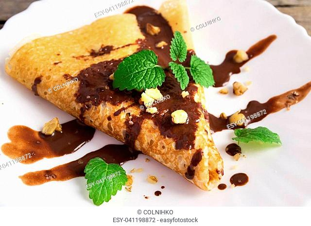 Pancake with chocolate and nuts, decorated with mint leaf Pancake with chocolate and nuts, decorated with mint leaf on a white plate