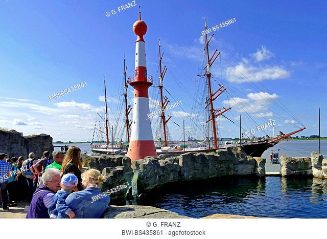 zoo Zoo am Meer with lighthouse Unterfeuer and masts of a sailer at Seebaederkaje, Germany, Bremerhaven