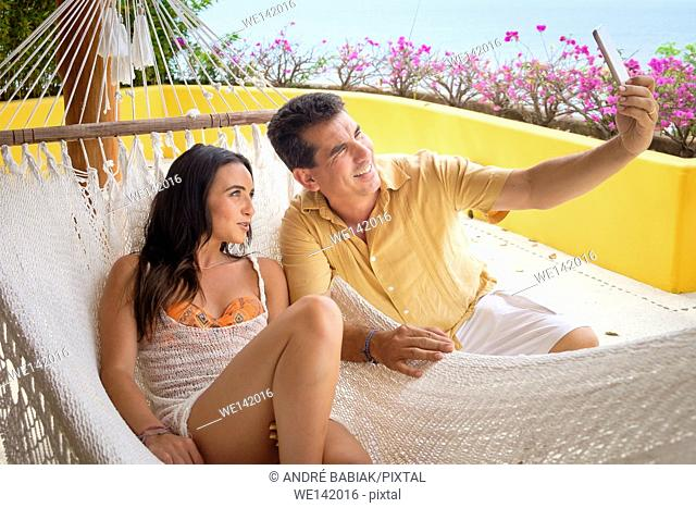 Man and woman enjoying a hammock on the terrace and taking a cell phone camera selfie