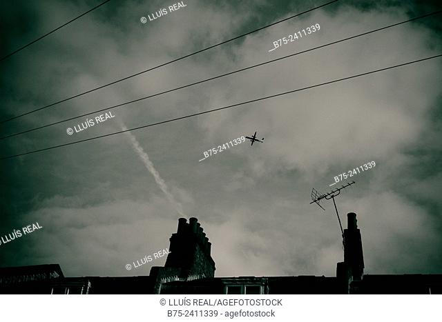 Sky view with clouds and an airplane flying and the silhouette of chimneys and TV antennas, plus electric wires, London, England, UK, Europe