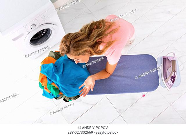 High Angle View Of Tired Housewife Woman Leaning On Ironing Board At Home