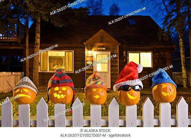 Jack-O-Lantern faces wearing stocking caps, stuck on top of the fence boards of white picktet fence with a house in background at twilight during Fall in...