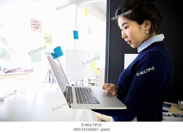 Businesswoman with laptop and adhesive notes at office glass