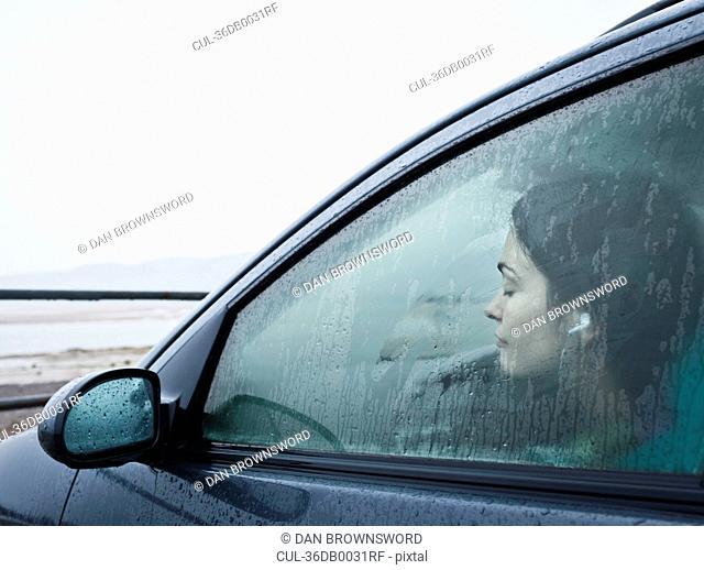 Teenage girl sitting in car by beach