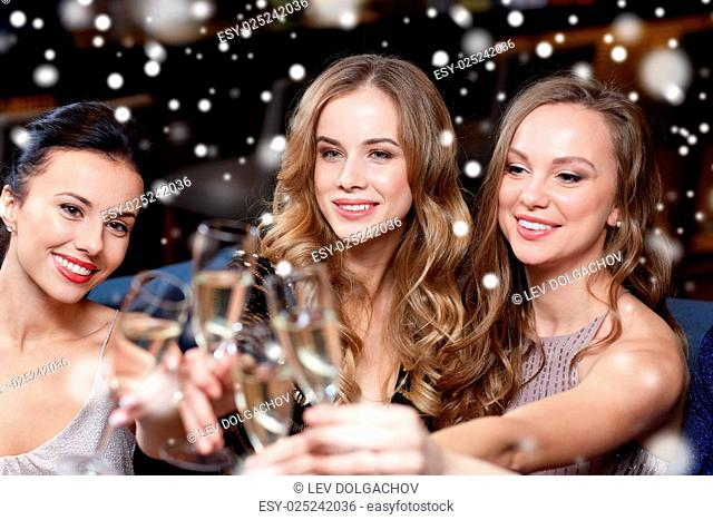 celebration, friends, new year, christmas and winter holidays concept - happy women with champagne glasses at bachelorette party at night club over snow