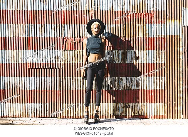 Young woman standing in front of striped wall
